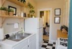 Открытые деревянные стеллажи в интерьере маленькой кухни в белой гамме