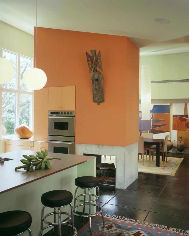 Ярко-оранжевая стена с камином в интерьере кухни