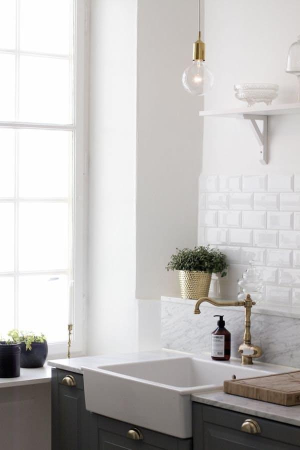 Сероватый мрамор подчёркивает белизну фона кухни белой и серой