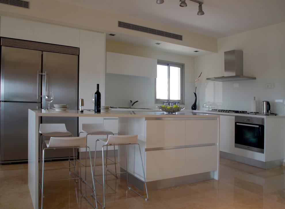 Белый островной стол с ящиками и столешницей в интерьере кухни