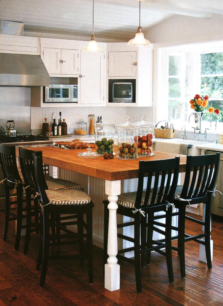 Островной стол с деревянной столешницей в интерьере кухни