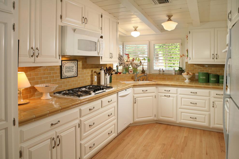 Белая кухня и столешница выложенная плиткой коричневого цвета