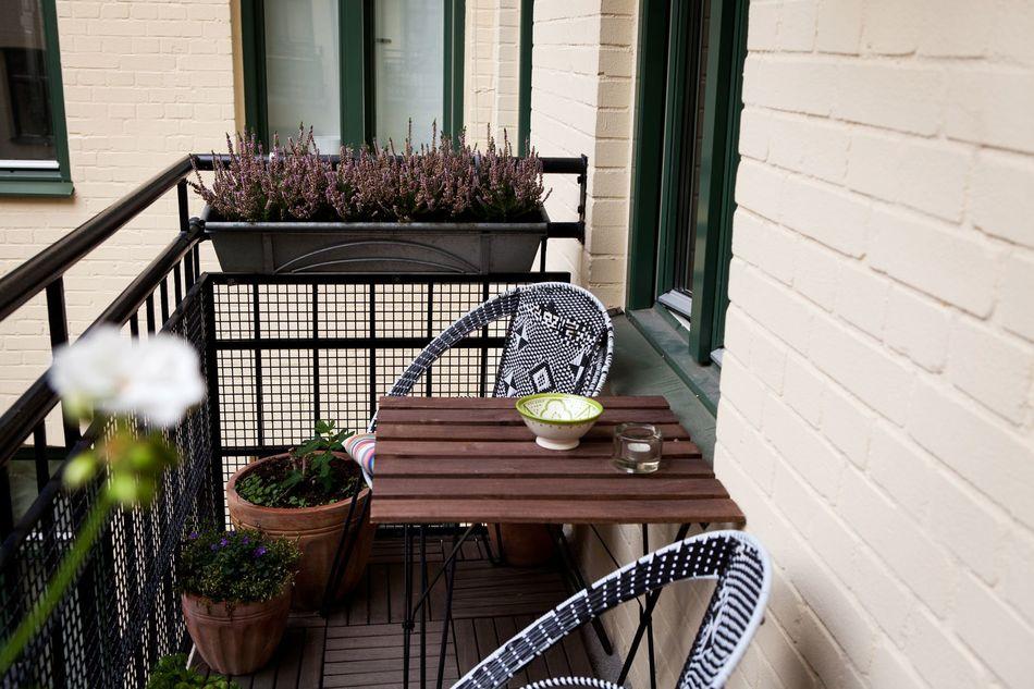 Кухонный балкон с плетёнными креслами и деревянным столиком
