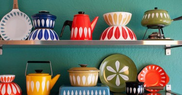 Яркая разноцветная эмалированная посуда на открытых стальных полках