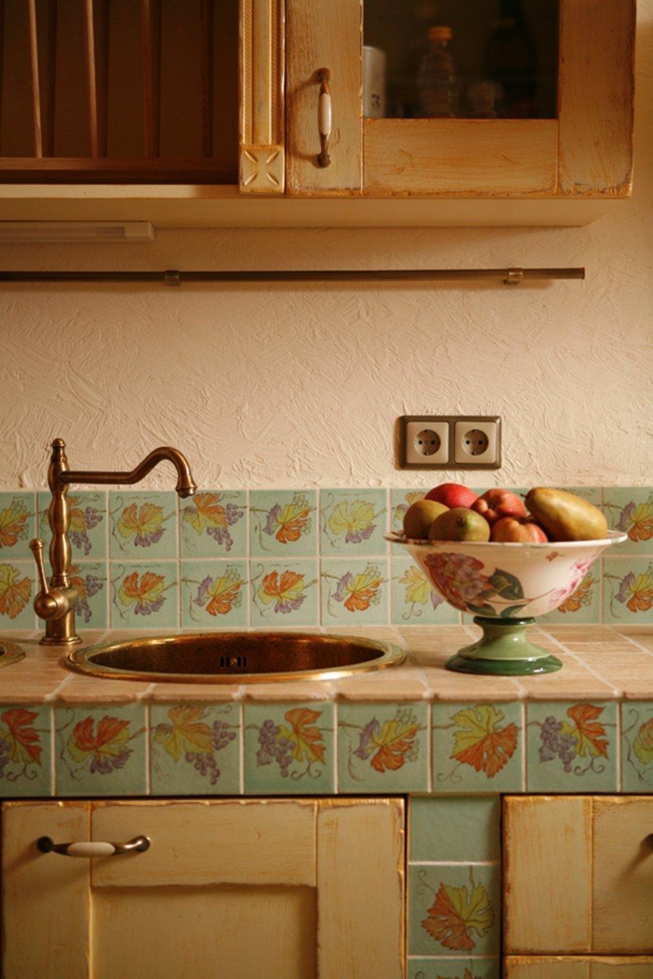 Медная раковина и смеситель на фоне кухонного фартука, оформленного плиткой в стиле прованс
