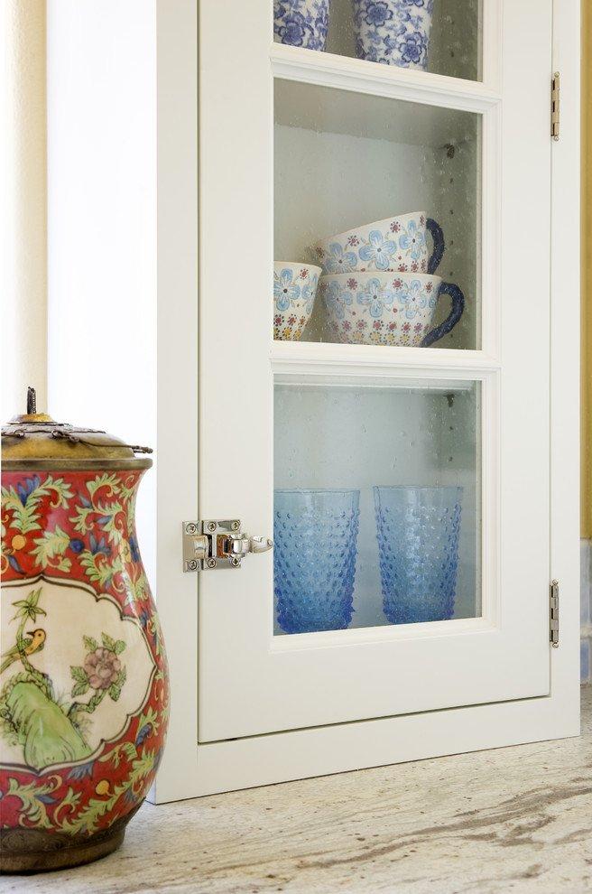 Керамическая посуда с цветочным орнаментом в кухонном серванте