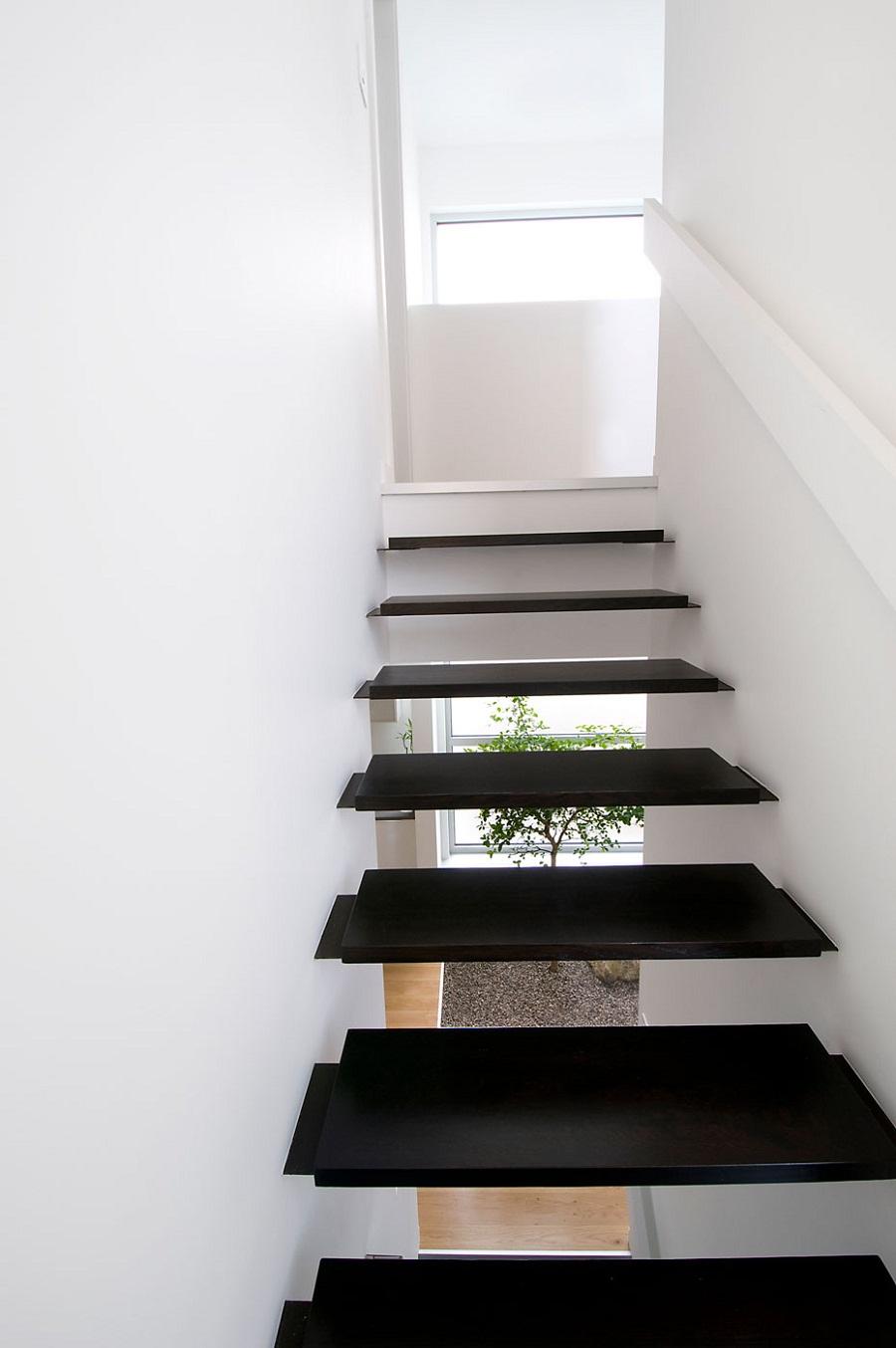 Чёрные ступени лестницы в белом интерьере