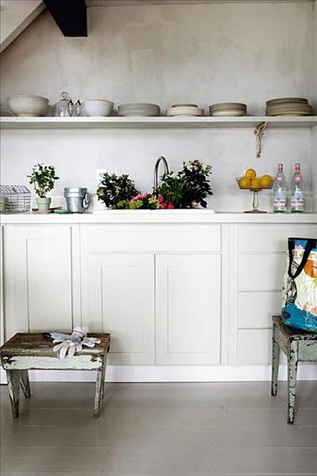 Открытые деревянные полки с керамической посудой в интерьере белой кухни