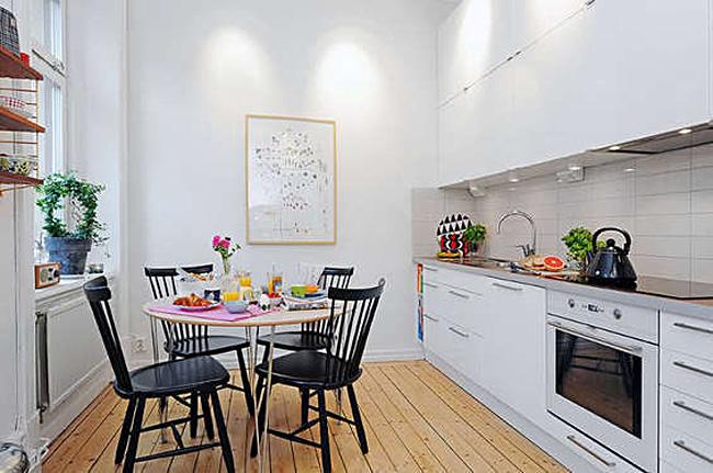 Чёрные стулья в интерьере белой кухни