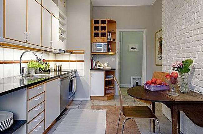 Грубая кирпичная стена в дизайне белой кухни