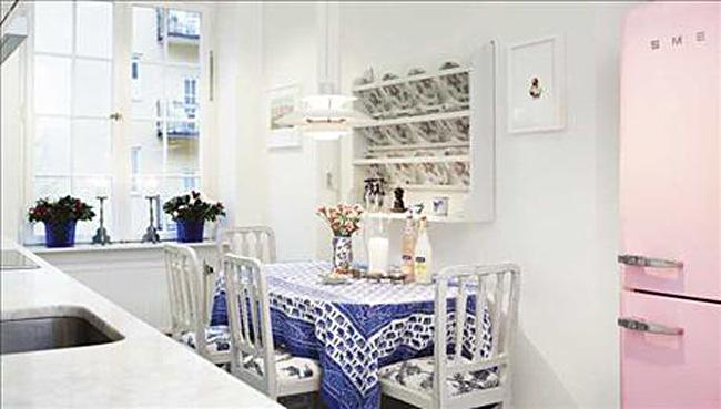 Яркая синяя скатерть на обеденном столе в интерьере белой кухни