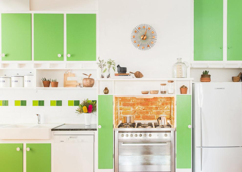 Кирпичная кладка стены за плитой в интерьере зелёной кухни