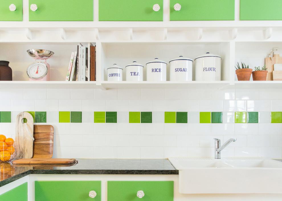 Белая с зелёными вставками плитка в оформлении рабочего фартука в интерьере кухни